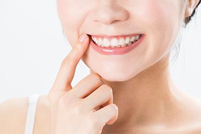 写真:白い歯でほほ笑む女性